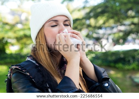 Outdoor portrait of beautiful girl with tissue having flu or allergy. - stock photo