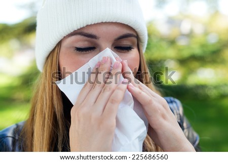 Outdoor portrait of beautiful girl with tissue having flu or allergy.