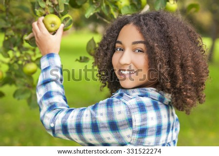 Outdoor portrait of beautiful happy mixed race African American girl teenager female child young woman picking an organic green apple in an orchard and smiling with perfect teeth - stock photo