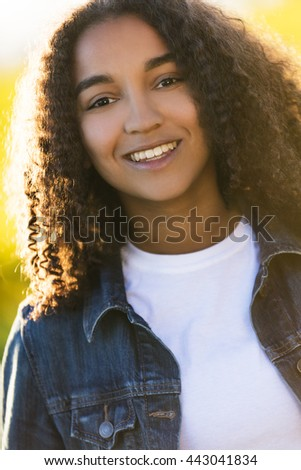 Outdoor portrait of beautiful happy mixed race African American girl teenager female young woman smiling laughing with perfect teeth in golden evening sunshine - stock photo