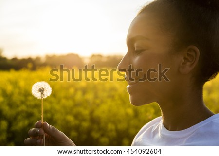 Outdoor portrait of beautiful happy mixed race African American girl teenager female young woman smiling in golden sunset light blowing dandelion clock flower - stock photo