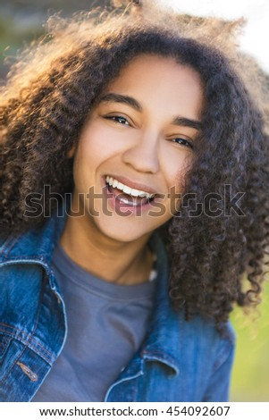 Outdoor portrait of beautiful happy mixed race African American girl teenager female young woman smiling laughing with perfect teeth