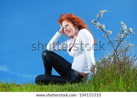 Outdoor portrait of beautiful readheaded girl resting on grass over blue sky at spring - stock photo
