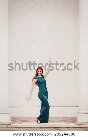 Outdoor portrait of beautiful redhead dancing woman