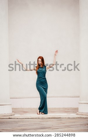 Outdoor portrait of beautiful redhead dancing woman - stock photo