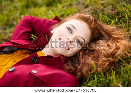 Outdoor portrait of beautiful redhead woman in red cloak
