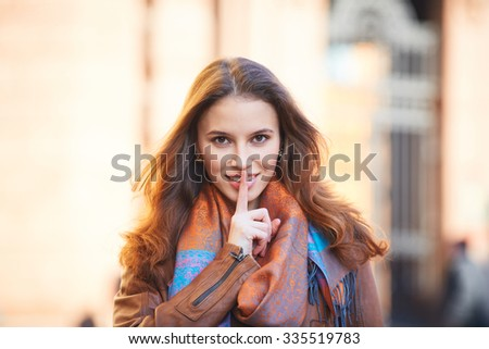 Outdoor portrait of beautiful redhead young woman covering her mouth with finger