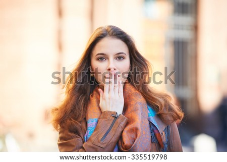Outdoor portrait of beautiful redhead young woman covering her mouth with hand - stock photo