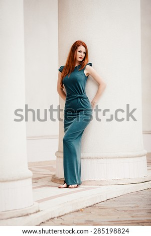 Outdoor portrait of beautiful redhead young woman near column - stock photo