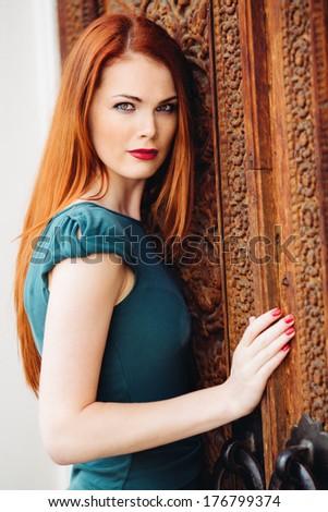 Outdoor portrait of beautiful redhead young woman near door - stock photo