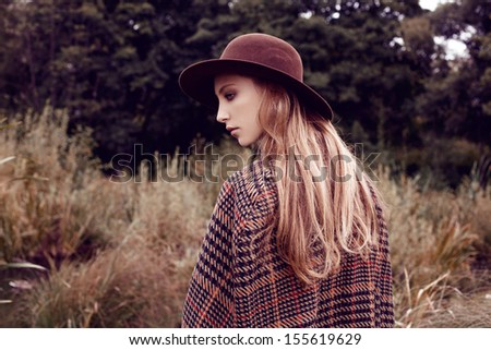 outdoor portrait of beautiful romantic girl with long hair. Dressed in coat and hat