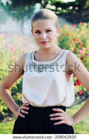 Outdoor portrait of beautiful stylish young woman wearing black skirt and beige silk blouse. Photo toned style instagram filters