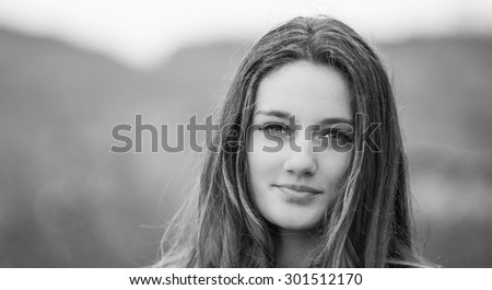 Outdoor portrait of beautiful teenage girl in spring in black and white. - stock photo