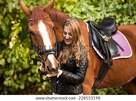 Outdoor portrait of beautiful woman feeding brown horse from hand - stock photo