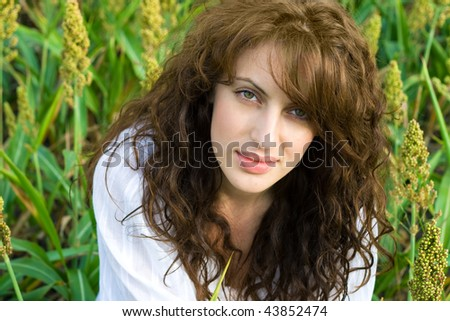 Outdoor portrait of beautiful woman in the field with wavy hair
