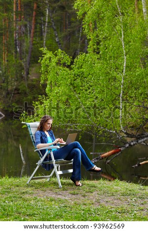 outdoor portrait of beautiful woman sitting in folding chair with laptop near the pond in forest - stock photo