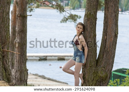 outdoor portrait of beautiful woman with bikini under overalls and braid hair-style posing near tree with blue sea water and jetty on background  - stock photo