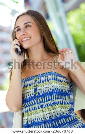 Outdoor portrait of beautiful young girl talking on mobile phone. - stock photo