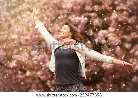 outdoor portrait of beautiful young woman under flying petals of blossom cherry trees - stock photo