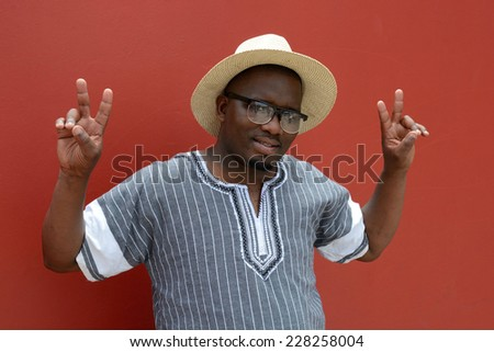 Outdoor portrait of black South African young man with happy smiling facial expression, wearing spectacles and hat and showing the victory sign with both hands in front of a blurry red wall.