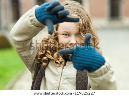 Outdoor portrait of blond teenager girl framing her view with the fingers