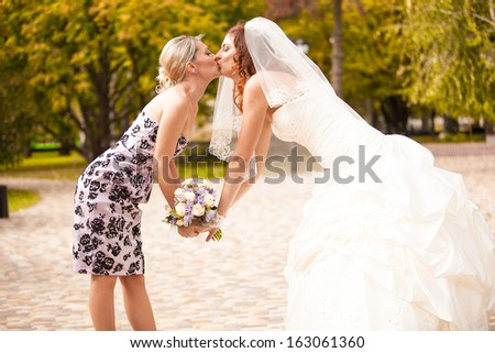 Outdoor portrait of bridesmaid kissing beautiful bride - stock photo