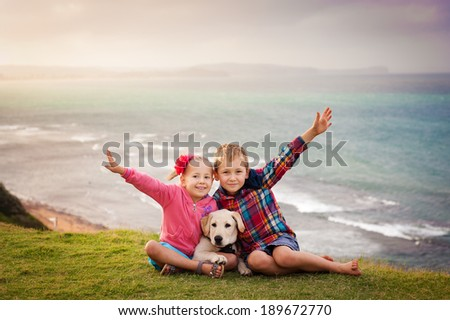 Outdoor portrait of brother and sister having fun with their pet dog labrador with ocean view - stock photo