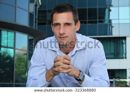 Outdoor portrait of businessman in front of modern office building