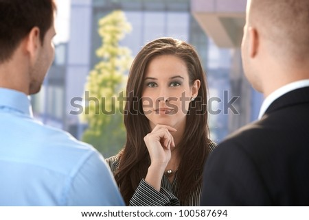 Outdoor portrait of businesswoman with colleagues, looking at camera, concentrating.