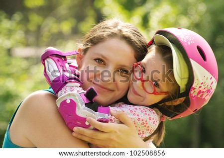 Outdoor portrait of caucasian mother and daughter wearing rollerblade protection and helmet.