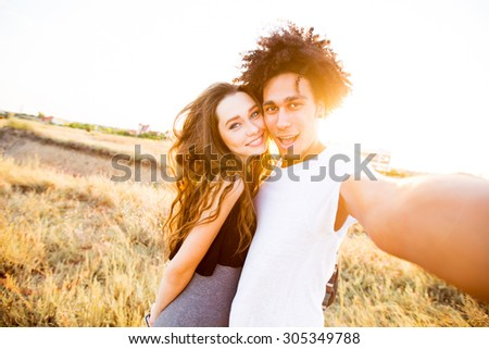 Outdoor portrait of  cheerful  young international couple shoes crazy  faces .  Friends having fun , emotional people, making self portrait.  - stock photo