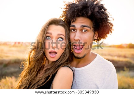 Outdoor portrait of  cheerful  young international couple shoes crazy  faces .  Friends having fun , emotional people, making self portrait.