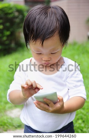 Outdoor portrait of child using a digital tablet or smart phone - asian - stock photo