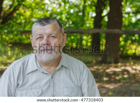 Outdoor portrait of comfortable senior man in light shirt