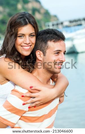Outdoor portrait of cute boy piggybacking girlfriend. - stock photo