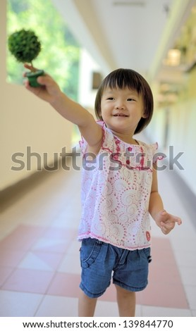 Outdoor portrait of cute little girl holding a plant   - stock photo