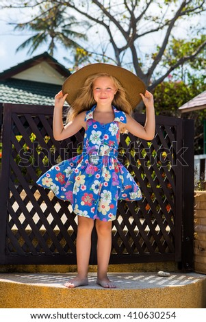 Outdoor portrait of cute little girl in blue floral dress and beach straw hat. Beautiful lady touch her big hat and smile. Summer sunny day. House with wooden fence at tropical background Mothers day. - stock photo
