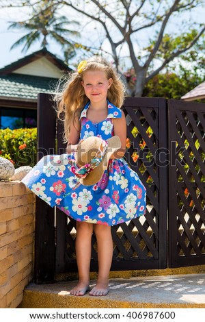 Outdoor portrait of cute little girl in blue floral dress. Beautiful lady hold beach straw hat in her hands and smile. Summer sunny day. House with wooden fence at tropical background. - stock photo