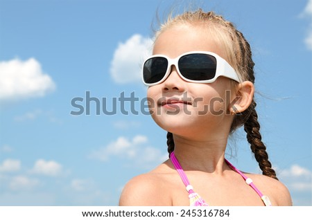 Outdoor portrait of cute little girl looking away in sunglasses