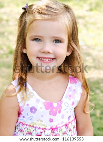 Outdoor portrait of cute little girl on the meadow