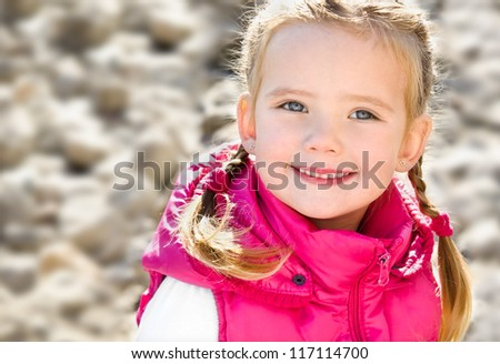 Outdoor portrait  of cute sitting little girl in spring day