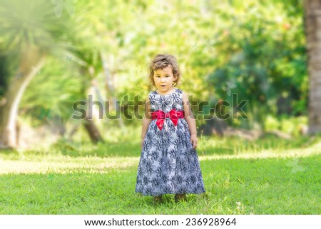 outdoor portrait of cute young child kid girl on natural green background - stock photo
