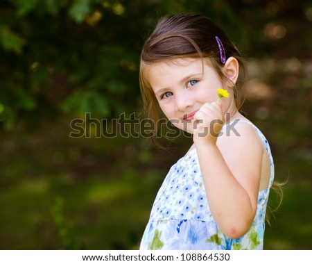 Outdoor portrait of cute young girl holding flower in park - stock photo