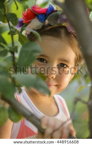 Outdoor portrait of expressive beautiful little girl wearing flower wreath. Healthy lifestyle concept - stock photo