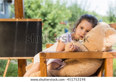 Outdoor portrait of expressive charming little girl hugging huge plush bear. Little child playing with teddy bear - stock photo