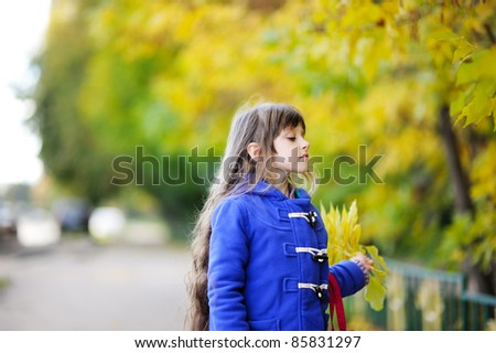 Outdoor portrait of funky little child girl in blue coat holding yellow leaves - stock photo
