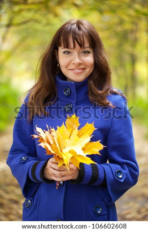 Outdoor portrait of   gilr with maple posy - stock photo