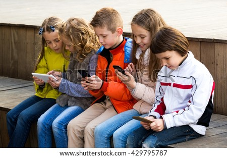 Outdoor portrait of girls and boys playing with smartphones and smiling