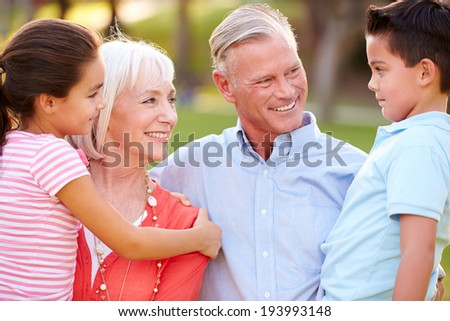 Outdoor Portrait Of Grandparents With Grandchildren In Park