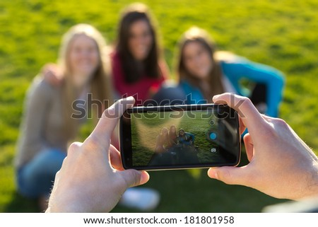 Outdoor portrait of group of friends taking photos with a smartphone in the park